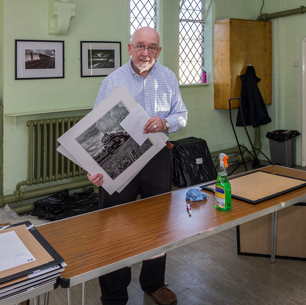 Len Harris with pictures to be framed